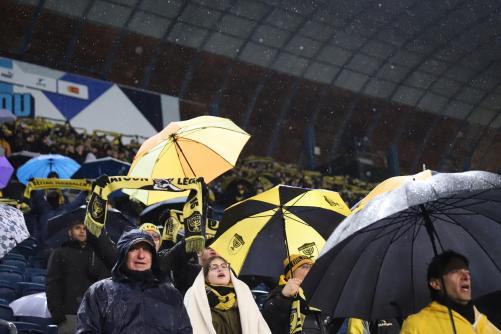 אוהדי ביתר ביציע עם מטריות בגשם