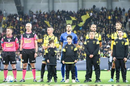 השחקנים עומדים עם ילדים לפני שריקת הפתיחה